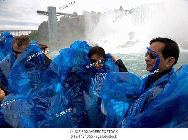 tourists getting wet in blue plastic waterproof ponchos at the maid of the mist niagara falls ontario canada