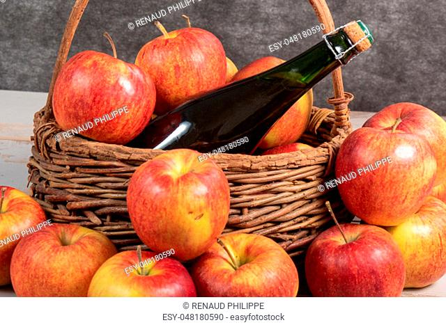a bottle of cider and beautiful organic apples
