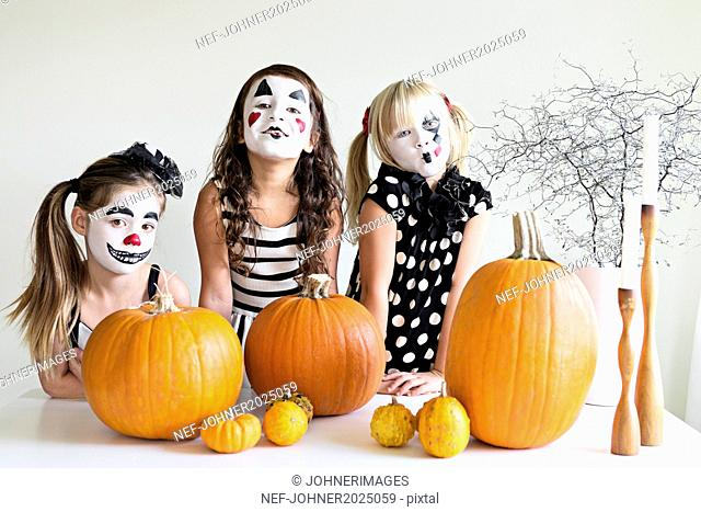 Girl with painted faces posing with pumpkins