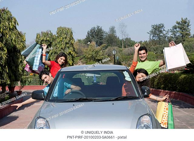 Friends carrying shopping bags in the car