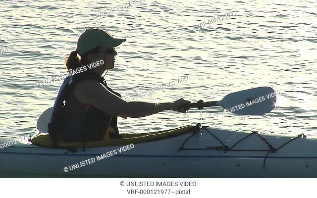 Silhouette of kayaker paddling in sunset