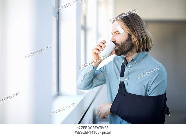 Employee with sling drinking coffee by the window