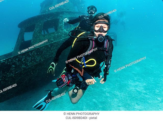 Underwater view of two divers in front of a wreck close to Phuket, Thailand