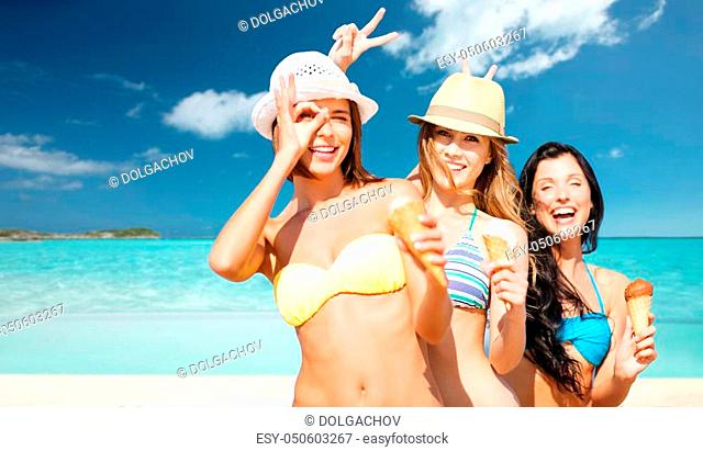summer holidays, vacation, food, travel and people concept - group of smiling young women in hats eating ice cream over exotic tropical beach with background