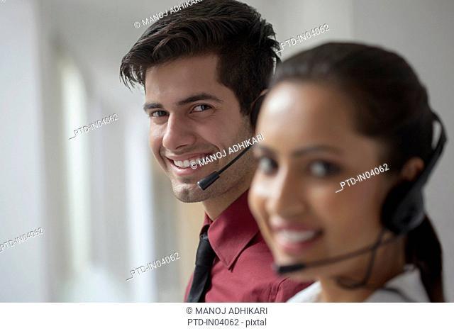 India, Male telemarketer sitting behind female telemarketer smiling