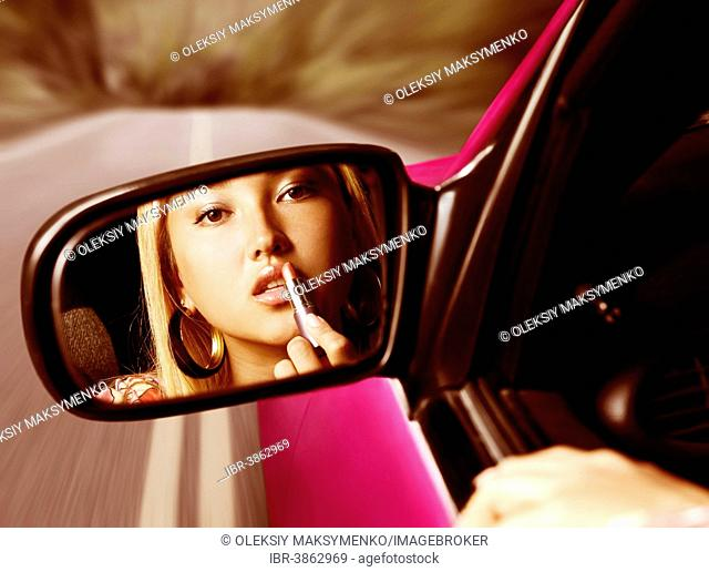 Young woman applying lipstick, looking in a rear view mirror, while driving on a highway