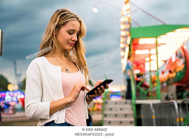Young woman using cell phone on a funfair