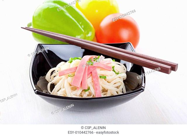 Tasty noodles with ham green onions in a beautiful black bowl on a white wooden background. Pepper and tomatoes