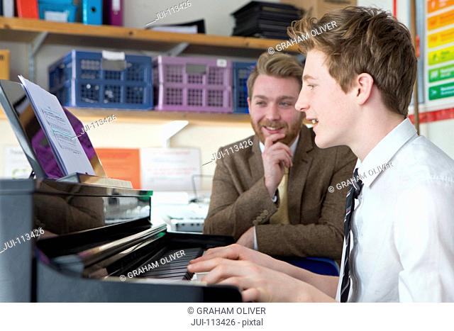Teacher teaching high school student playing piano in music classroom