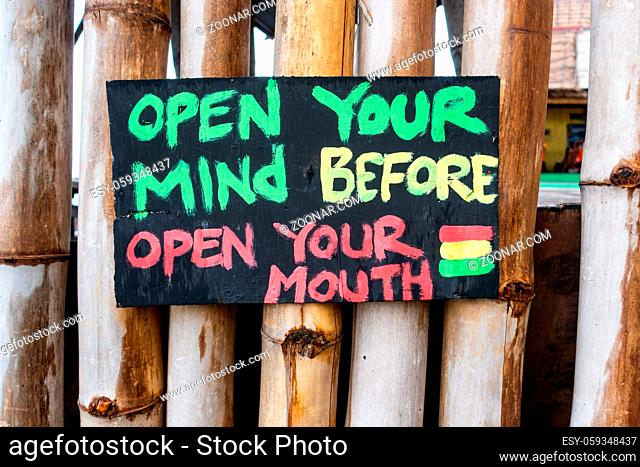 Handmade painted sign reads open your mind before open your mouth