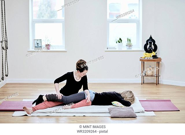 Woman receiving a Thai massage from a practitioner