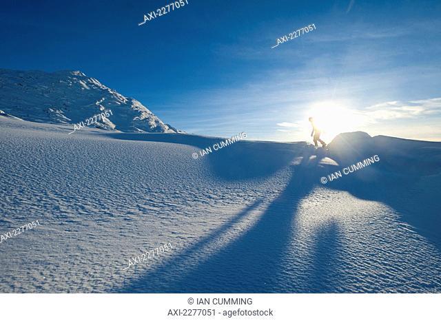 Walker going through heavy snow up Beinn Respiol, Ardnamurchan peninsula; Highlands, Scotland