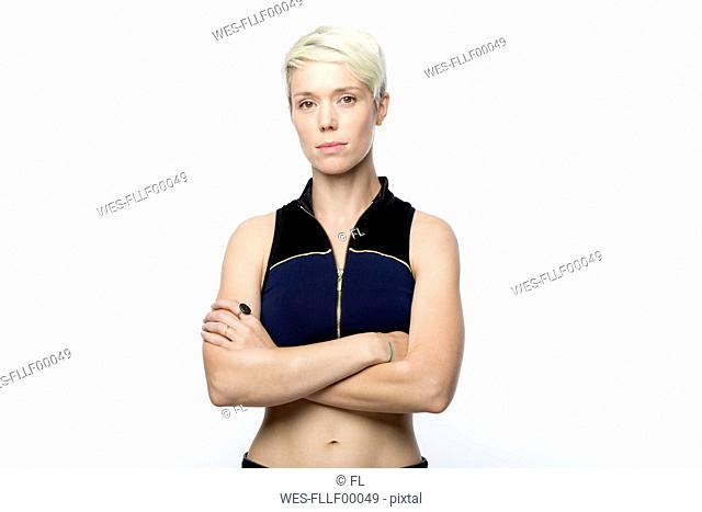 Portrait of serious looking woman with short blond dyed hair in front of white background