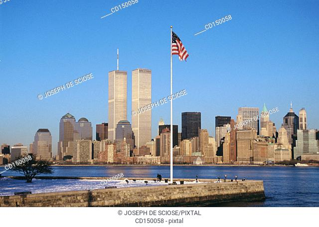 Historic view of the lower New York City skyline showing the Twin Towers of the World Trade Center with the tip of Ellis Island and an American flag on a pole...