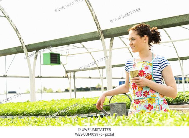 Young female gardener taking a break from watering plants in nursery