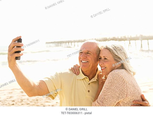 Senior couple taking picture of themselves on beach