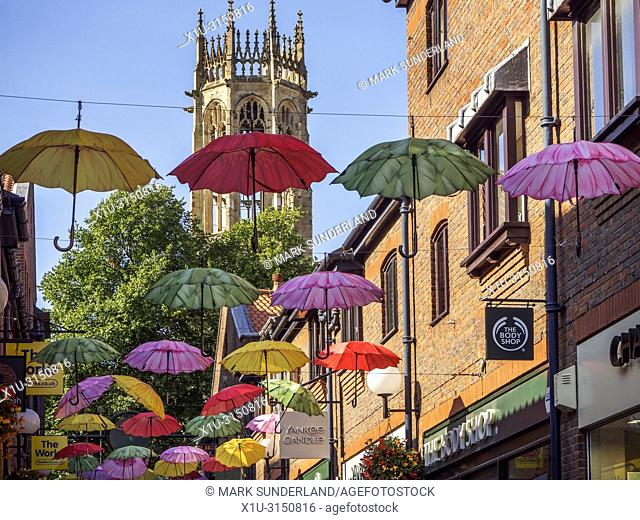 Colourful umbrellas across Coppergate with All Saints Pavement church tower behind York Yorkshire England