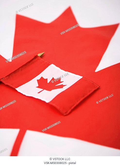 Canadian flag on large maple leaf symbol