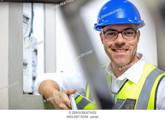 Portrait of smiling electrician at fuse box