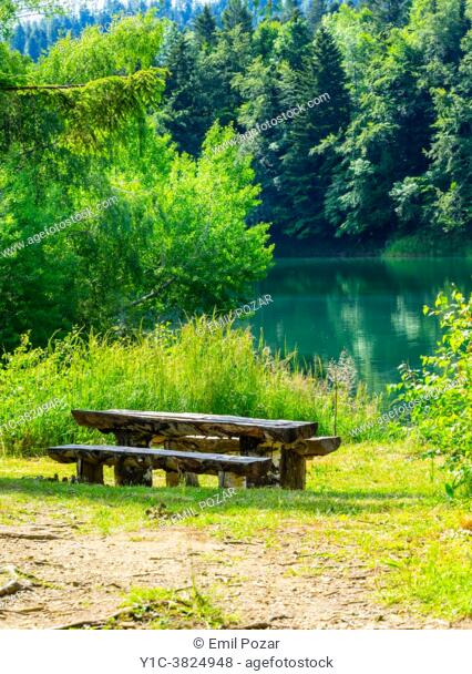 Wooden benches and table Lokve lake near Mrzla vodica in Croatia