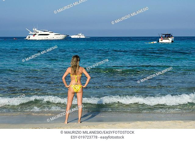 Blonde girl looking boats on the sea blue and green to the beach