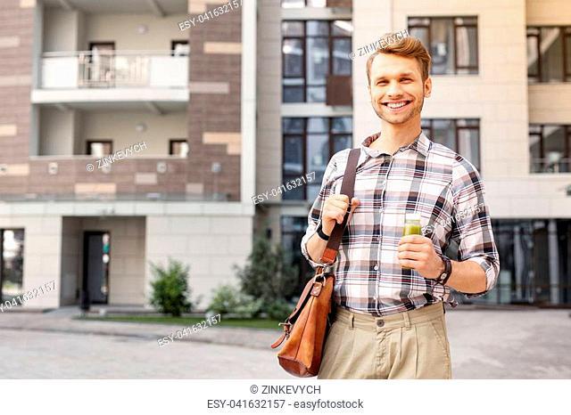 Great mood. Happy joyful man smiling while holding a bottle of smoothie