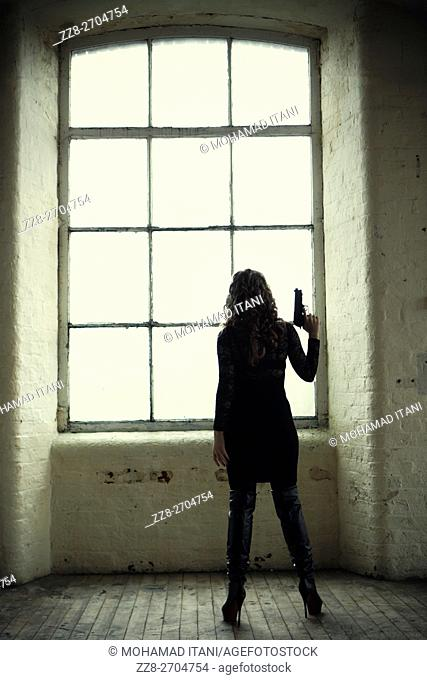 Woman holding a gun by the window