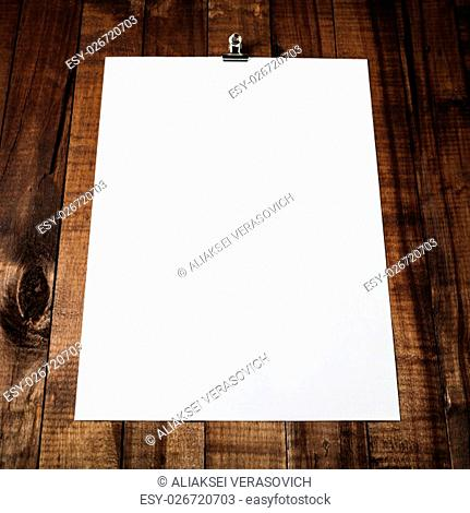 Blank white letterhead on vintage wooden table background. Blank letterhead with plenty of copy space. Mock-up for design portfolios