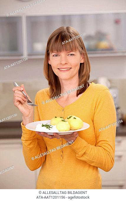 Woman eating boiled potatoes with quark