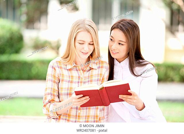 International student and domestic student in college reading a book together outside on campus
