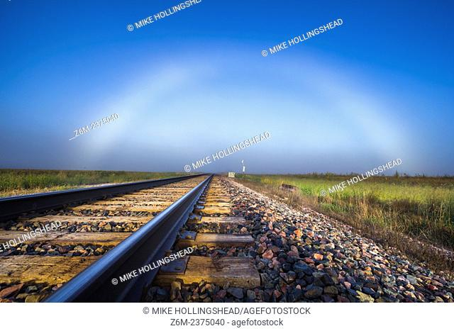 Fogbow forms in western Iowa over some train tracks