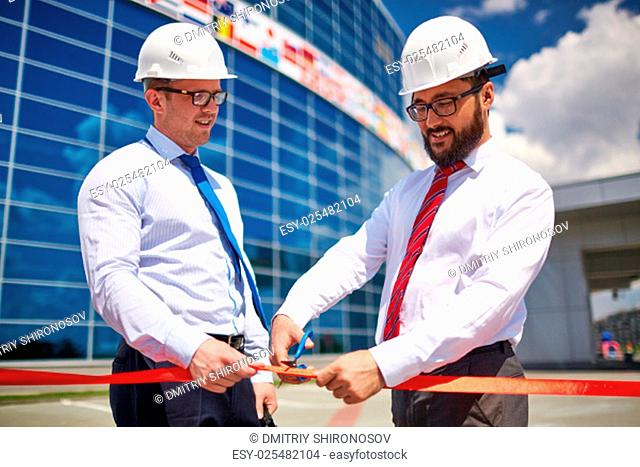 Happy architect cutting red ribbon outside with his co-worker near by