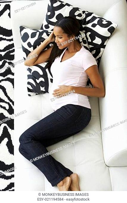 Overhead View Of Pregnant Woman Relaxing On Sofa
