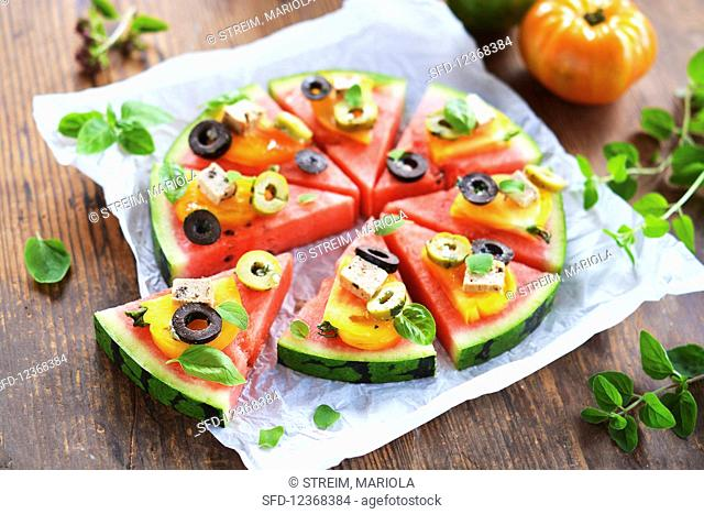 Melon pieces garnished like a pizza with tomatoes, tofu, olives and fresh herbs