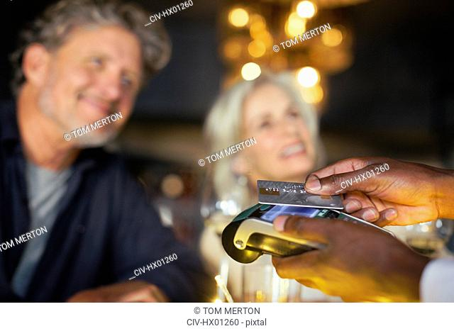 Close up couple paying waiter with credit card reader