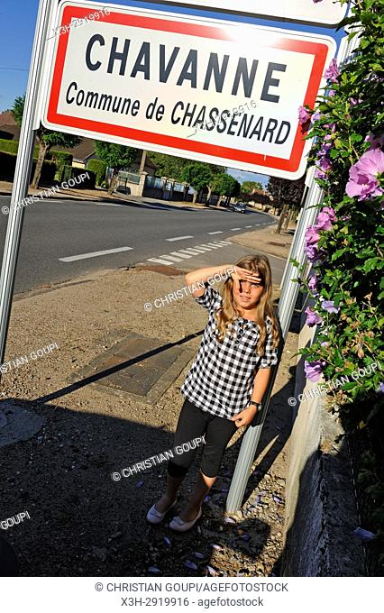 little girl under a road sign at the entrance of a village in Allier department, Auvergne-Rhone-Alpes regionFrance, Europe
