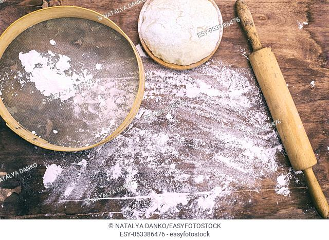 yeast dough in a wooden bowl and a round vintage sieve with a rolling pin, top view