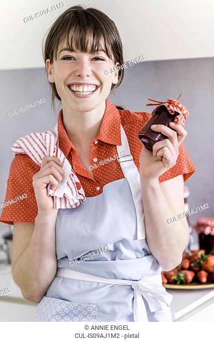Woman holding up jar of homemade strawberry jam