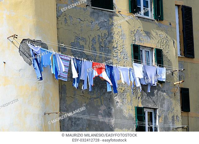 Clothes hanging to dry in the sun on the facade of an old palace of Camogli Italy
