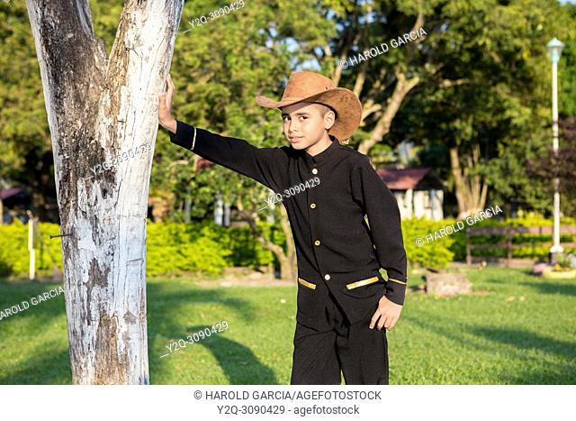 Young man in black cowboy clothes and hat posing for camera in a photo shoot