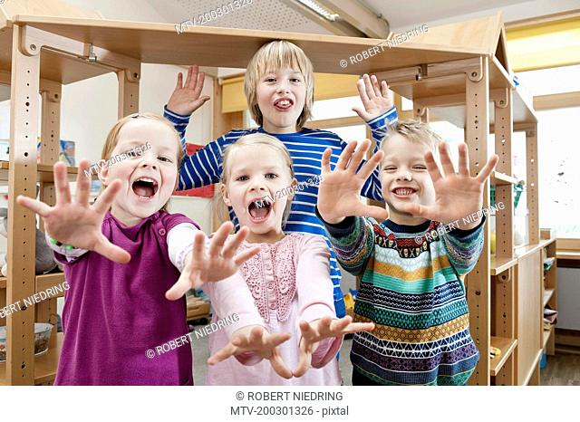 Four children with outstretched arms screaming