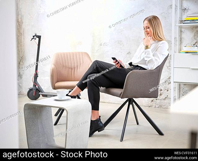 Relaxed businesswoman using cell phone in modern office with electric scooter in background