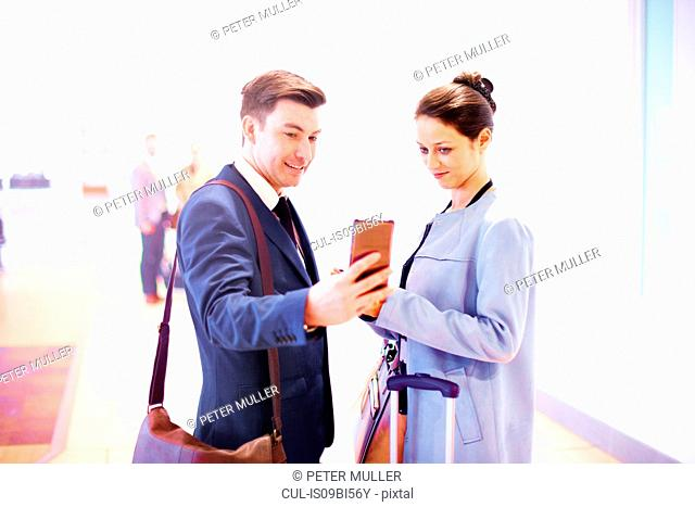 Young businesswoman and man in airport looking at smartphone