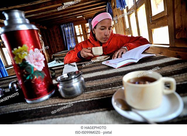 Woman reading guidebook at teahouse, Yak Kharka, Nepal