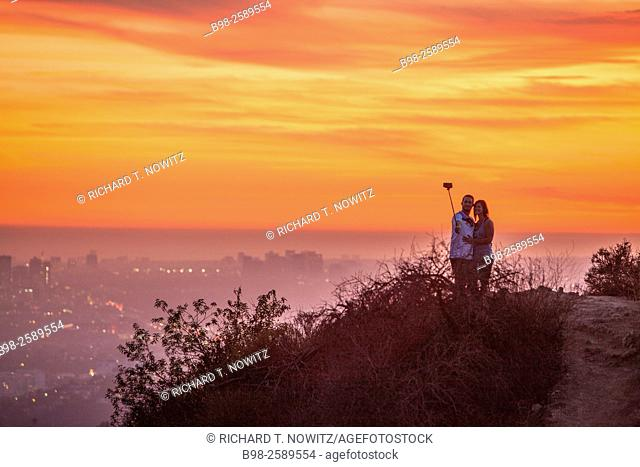 A couple using a selfie stick at sunset in Griffith Park in the Hollywood Hills overlooking Los Angeles