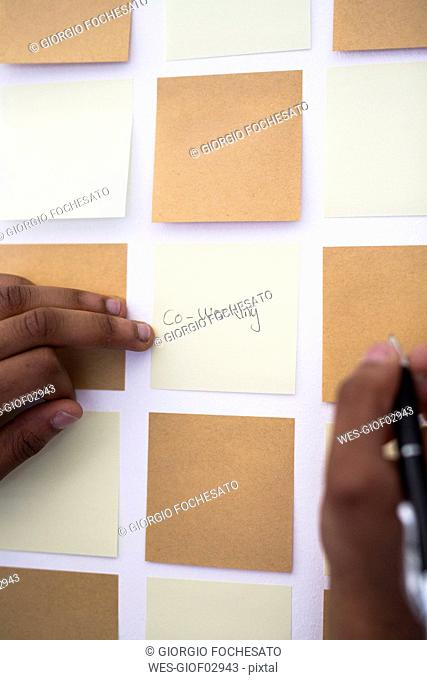 Writing on adhesive note at wall in office