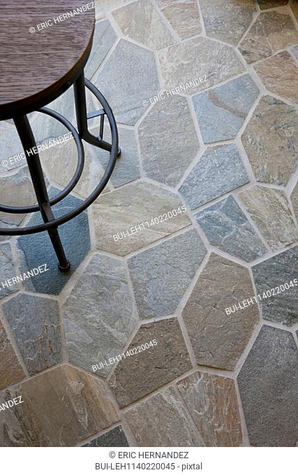 Close-up of stone floor with cropped stool at home