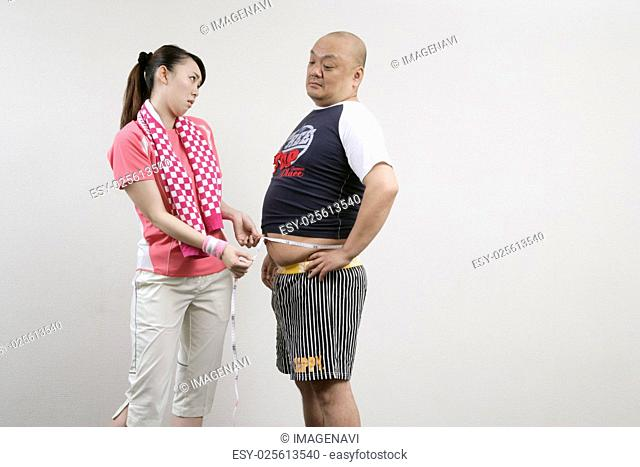 Woman measuring man's belly
