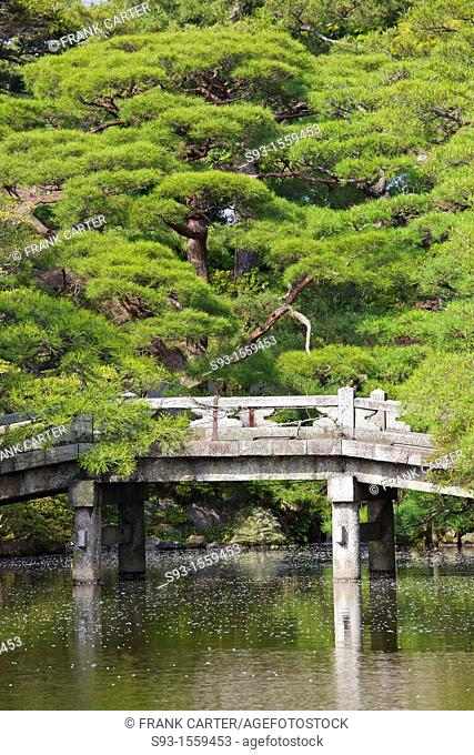 A stone arched Japanese bridge in a garden inside the Imperial Palace