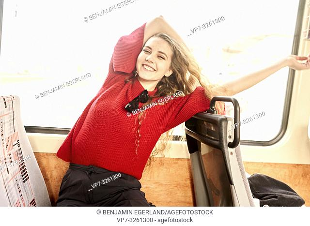 young happy woman in public transportation, in city Cottbus, Brandenburg, Germany